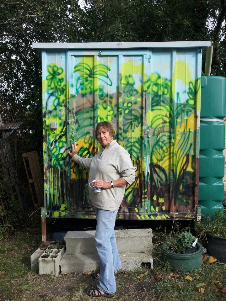 Artist Ruth Hartley stands at the door of her studio made from a metal container on stilts. The front of the container is a brightly painted landscape of green and yellow plants against a light blue sky.