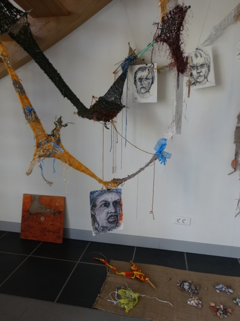 Art by Ruth Hartley: View of the Surviving Monsters installation at the Corpus exhibition at La Peleyre Gallery, France, consisting of suspended knitted scarves in brown and yellow representing the Road, black-and-white drawings hanging from the Road and shells, stones and other objects collected along the journey lying on a piece of hessian on the floor