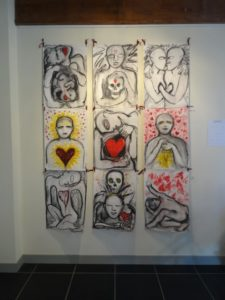 Art by Ruth Hartley: 9 charcoal drawings arranged in a 3 by 3 grid with highlights in reds and yellows. A theme of hearts repeats in each drawing.