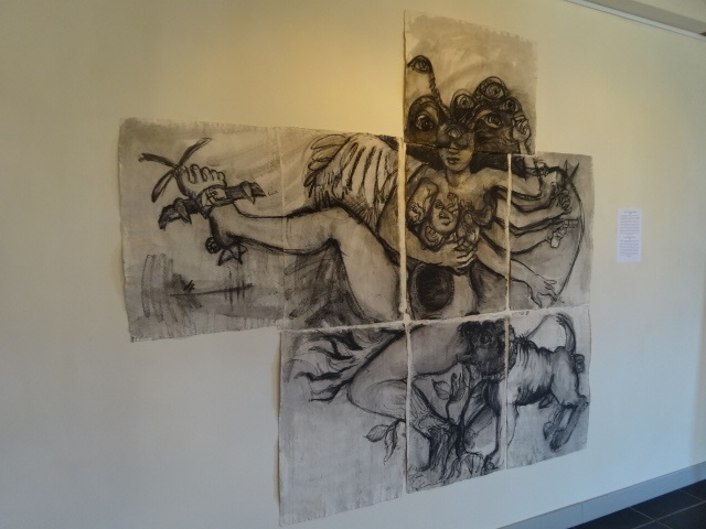 Art by Ruth Hartley: A charcoal painting of Medusa over a grid of 7 canvases. She has multiple arms, one wing, multiple breasts and an open womb. Her right leg is tied down and her left leg rooted in the ground. A powerfull looking dog is barking at her side.