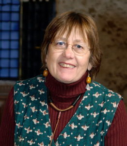 Ruth Hartley smiles at the camera. Her expression is friendly, pleased and engaging, inviting contact.She wears light-rimmed spectacles, a red-brown ribbed roll-neck top with a dark green-and-cream patterned pinafore over it, as well as ochre earrings and a black-and-ochre necklace.