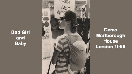 Black and white image of a young woman in a striped t-shirt with baby in a cloth carrier on her back at at demonstration outside Marlborough House in London in 1966. She wears sunglasses and had her hair tied back. A policeman stands in the background next to a placard bearing the words SOUTH WEST AF...