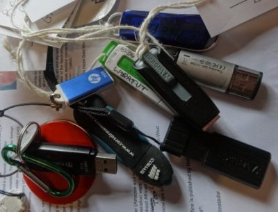 A jumble of USB sticks for storing work lie on a scrap of paper