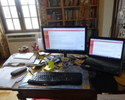The photo shows a laptop on the right, a large screen in the centre, blue and white mug of tea, yeoow post-it notes and pens in front of a sunny window and full bookshelf.