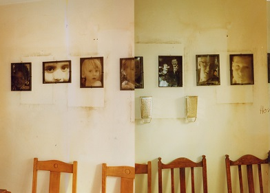A row of chairs sit below a row of transparent family photos lined up on a wall marked by the stains made by the removal of previous photos. The eyes of all the people in the photos are lined up so that one can see the family resemblances between the children and the photos of their parents as children