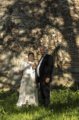 A man and woman holding champagne glasses stand in front of a tower with a tree shadow on it