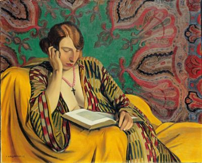 A woman in a Turkish dressing-gown reads a book sitting on  a chair draped in a yellow cloth in front of an exotic wall hanging
