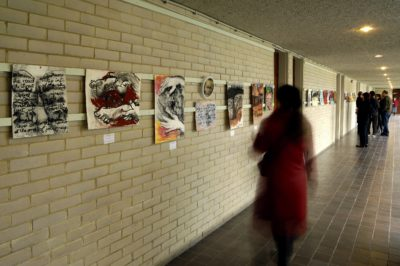 A woman in a red coat studies a row of drawings on a pale brick wall as she walks past. Her image is blurred as it is a time lapse photograph by Douglas Atfield