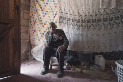 An old white-haired Zambian man in a suit with a medal bar on hs chest sits on a stool in his concrete block house with his possessions arounf him. Behind him his bed is hidden by curtains.