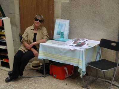 Ruth sits a table on which are her novels against a wall in the street outside a bookshop