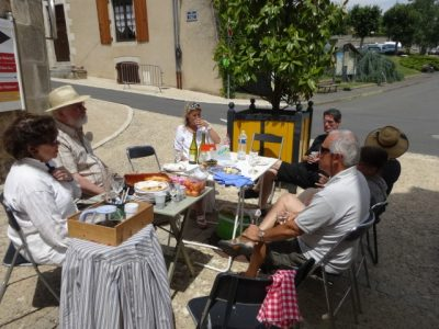 A group of people arounda table eating an informal meal in the street