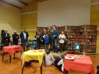 The author stands in the middle of a group of children in front of a screen that looks like a bookcase. The village mayor stands on his right.