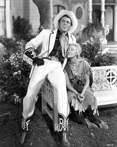 The photo shows a handsome cowboy in a snazzy white suit and stetson leaning on a garden bench on which sits a scruffy and dirty hillbilly girl with a blond plait and a dirty face. She is in love with the cowboy.
