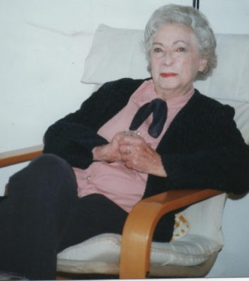 Rica sits in a Swedish-style chair wearing a black suit with a pink blouse. Her hands are clasped and her hair is white. Her face shows that she has had treatment for skin cancer.