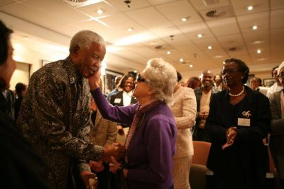 Nelsonn Mandela leans towards Rica holding her hand. Rica's hand cups Madiba's cheek affectionately.