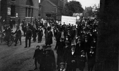 A group of working-class men, women and children in their best clothes walk down Bow Road with placards and banners in the rear.