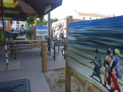A photgraph of African women walking along a beach is displayed next to a cafe terrace