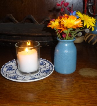 The photo shows a lit memorial candle and a few flowers in a small vase.