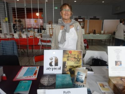 Ruth stands behind a display of her published books with her new novel and imprint on display