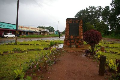 The photo shows the memeorial in a lsightly scruffy park after a tropical rainstorm. In the background are single story African shops with verandahs typical of a small African town