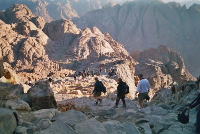 A group of pilgrims make their way down a steep rocky path into a gorge from the summit of Mount Sinai