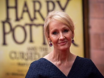 JK Rowling stands in front of a Harry Potter poster