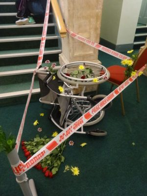 An overturned wheelchair rests at the bottom of a flight of stairs surrounded by floral tributes