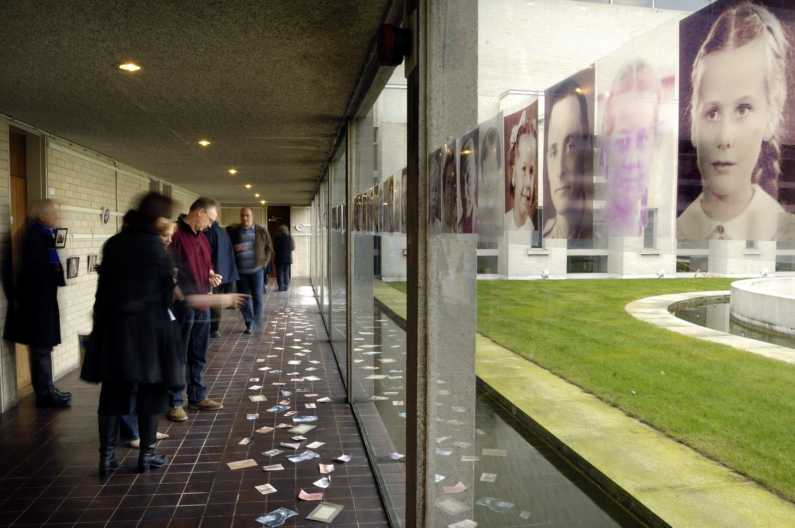 Art by Ruth Hartley: Ruth participated the Mother Art exhibition. This photo by Douglas Atfield shows visitors to the exhibition looking at postcards scattered on the floor of a long corridor alongside a glass wall with portraits hanging. The portrait nearest to the viewer is of a young girl.
