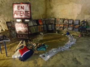 Art by Ruth Hartley: An art installation in the Corpus exhibition in Peleyre, France, consisting of many drawings hanging on two walls in the corent of a room. There are also two signs hanging from a stand, reading EN ATTENIE and BORDER CONTROL FRONTIER. Additional paper drawings are held on the floor by small white rocks.