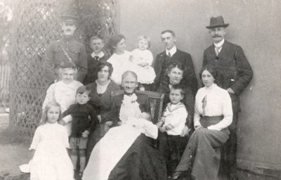 The photograph shows 4 generations of the Burton family seated in 3 rows round Great-Grandmother Burton who holds the youngest baby on her lap. The man on the top left is in a soldier's uniform