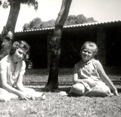 Two young sisters underneath trees on the lawn in front of a verandahed building with a corrugated asbestos roof.