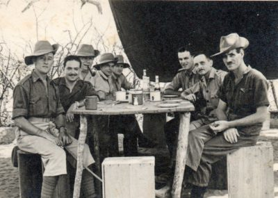 The black and white photo shows 8 men in uniform around a rough table under a canvas shelter — They have long shorts and felt bush hats
