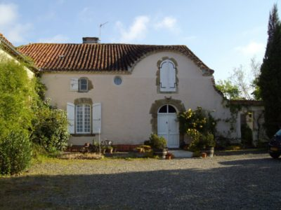 The photo shows a French farmhouse with pink walls and an arched front door set in a garden