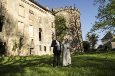 A couple in evening dress with champagne glasses in front of a ruined chateau.