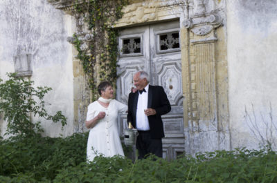 A man and woman in evening dress holding champagne glasses by the front door of a ruined chateau in a bed of nettles
