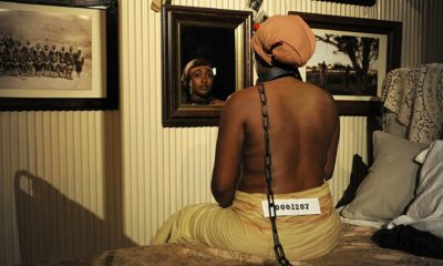 A young black woman naked from the waist up sits on a bed and looks at herself in the mirror. She has an iron collar and chain around her neck and a number fastened to her clothes.