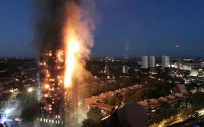 Grenfell Tower burning against the night sky above the city, one side is completely aflame