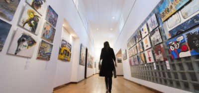 A woman in black is silhouetted as she walks down a long gallery with paintings on either side
