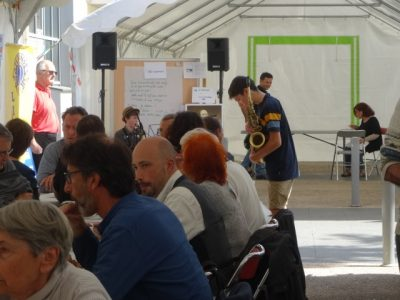 People sitting at a table eat lunch while two teenagers play jazz saxaphone