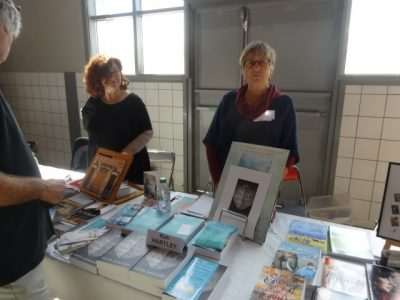 Clara and Ruth stand behind a table on which their books are displayed
