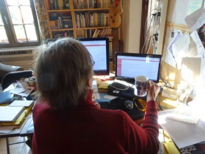 The image shows the writer from behind as she stares at her screen and holds a blue and white mug