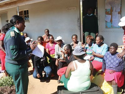 A prison officer in a green uniform holds a list of names on a sheet of paper and talks to a group of women prisoners seate on the ground