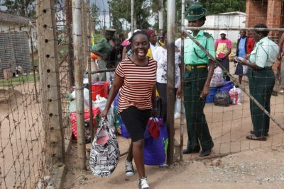 A young woman grinning happily walks out of the prison gates at Chikarubi watched by a prison officer