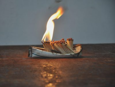 A small boat made from a bicycle mudguard has a cargo of burning matches