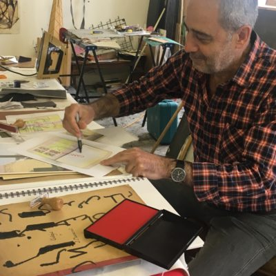 A grey-haired artist in a red and black check shirt draws at a table in his studio