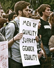 "A young bearded man with a backpack holds a banner which says ""Men of quality support Gender Equality."