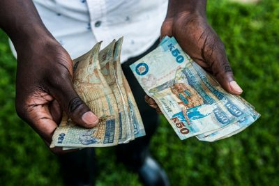 A man holds new bank notes in his left hand and old bank notes in his right hand
