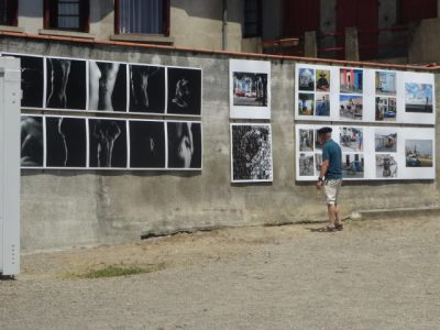 A man is looking at a serie of photographs displayed outside on a courtyard wall