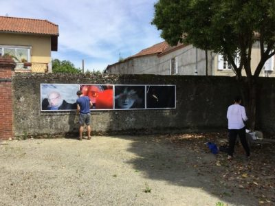 Two men are busy installing 4 large photographs on a stone wall.