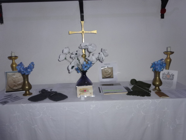 On the white altar are vases of forget-me-nots and white poppies, a pair of knitted mittens and a scarf in army green